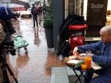 Straatbeeld: Ontbijten in de regen, voor de televisie