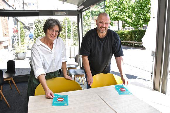 Dominik Daeninck en Sabine Wancour maken met flyers duidelijk welke tafels niet gebruikt mogen worden.
