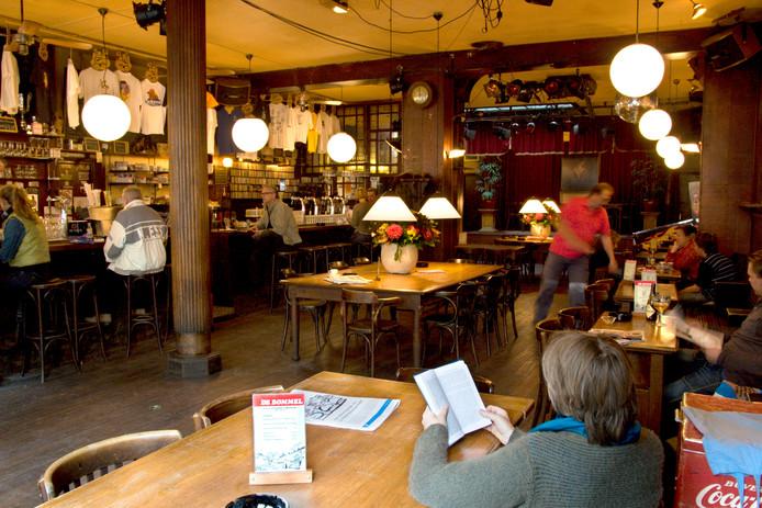 Anoniem aan een tafeltje. Café De Bommel past zich aan aan het moment van de dag.