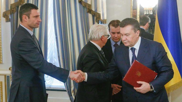 De voormalige president van Oekraine Viktor Janoekovitsj (R) schudt de hand van oppositieleider Vitali Klitsjko Beeld EPA