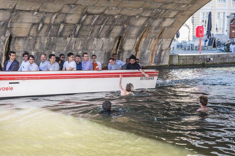 Een zwemmer geeft een toerist een high five.