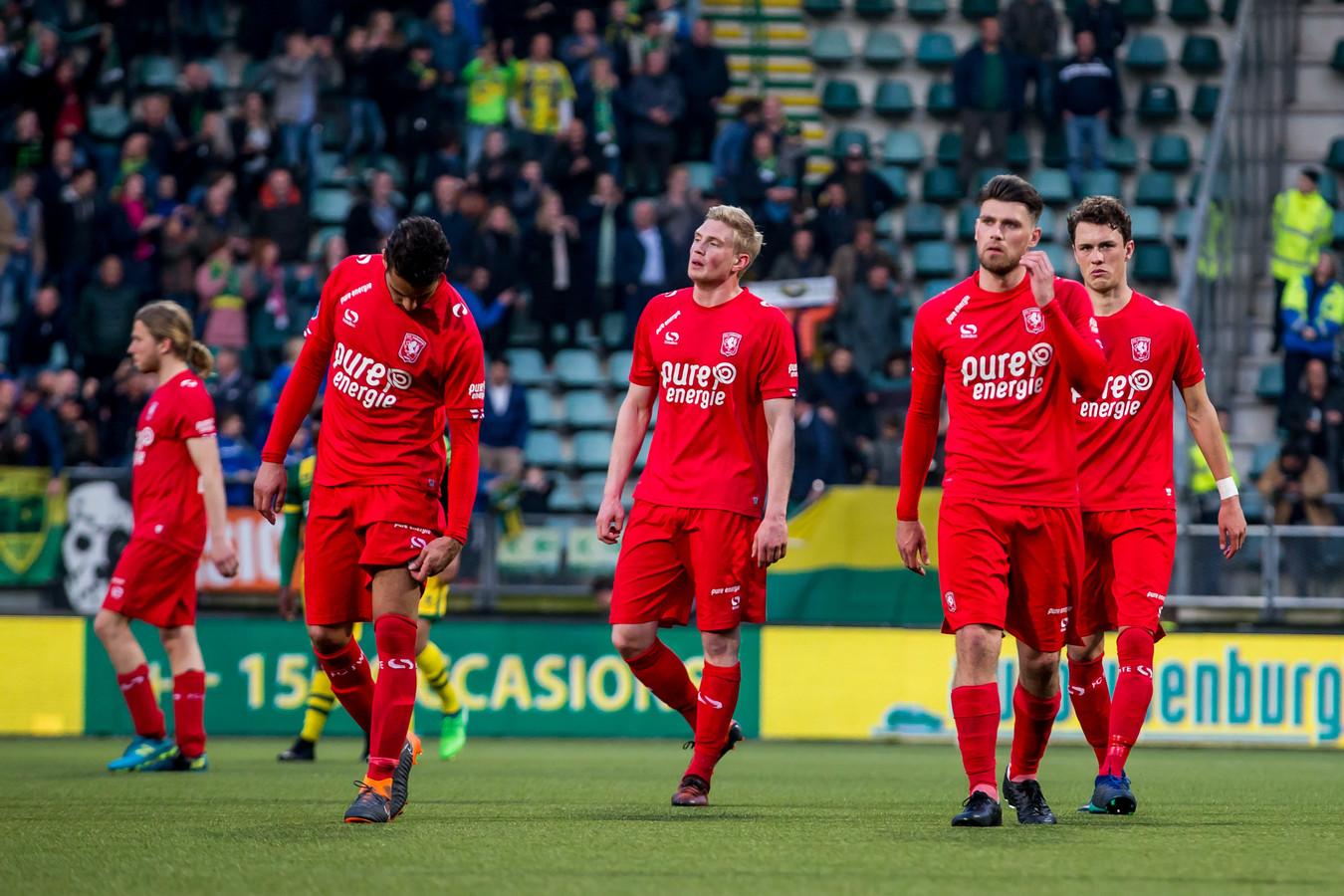 De spelers van FC Twente lopen teleurgesteld van het veld na de nederlaag tegen ADO Den Haag.