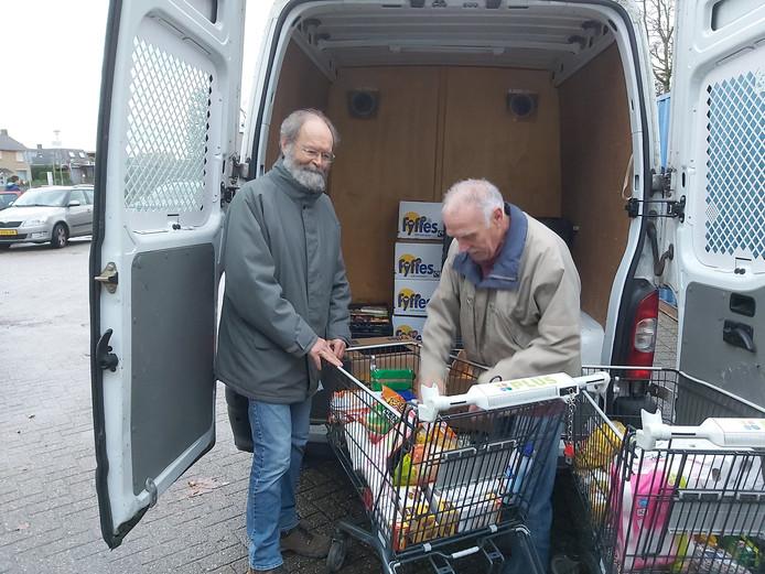 Piet Heisen (links) en een van de andere vrijwilligers laden de ingezamelde boodschappen in.