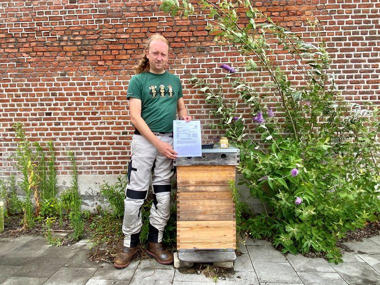 Imker Bart Lenaerts aan de bijenkast met de resultaten van de loodwaardenanalyse.