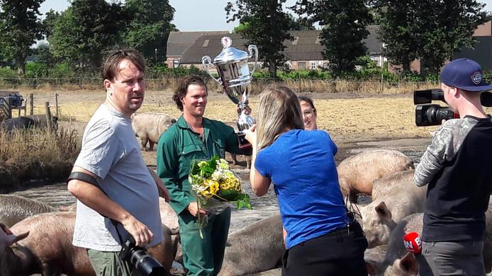 Boer Bas Antonissen toont de Modderpoeltrofee aan de verzamelde media, terwijl achter hem de varkens genieten van de modderpoel.