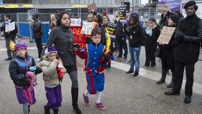 Een vrouw met drie kinderen passeert de demonstranten op weg naar het sinterklaasfeest in de Jaarbeurs.