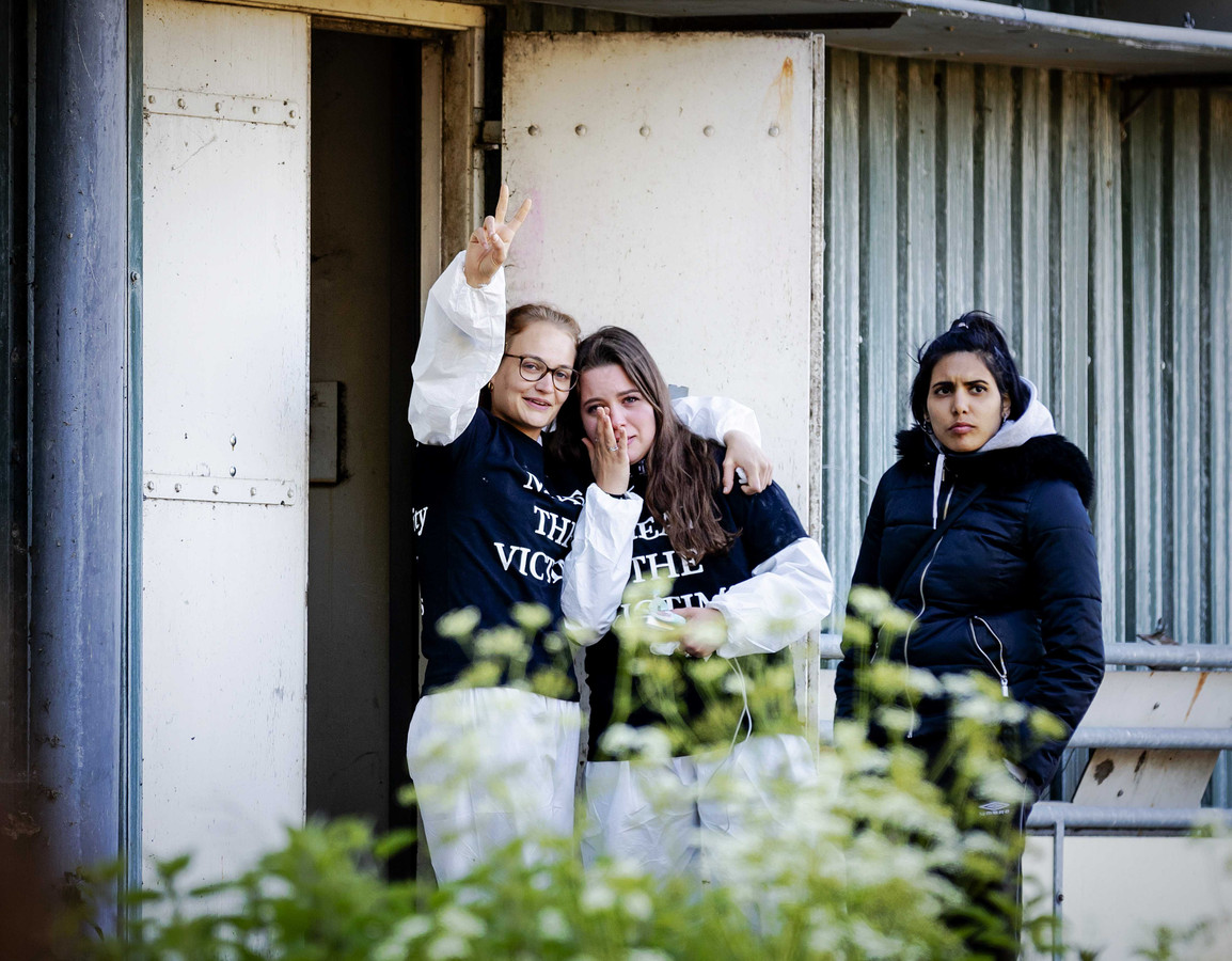 Dierenrechtenactivisten kijken uit de deur van de stal die ze bezet hebben in Boxtel.
