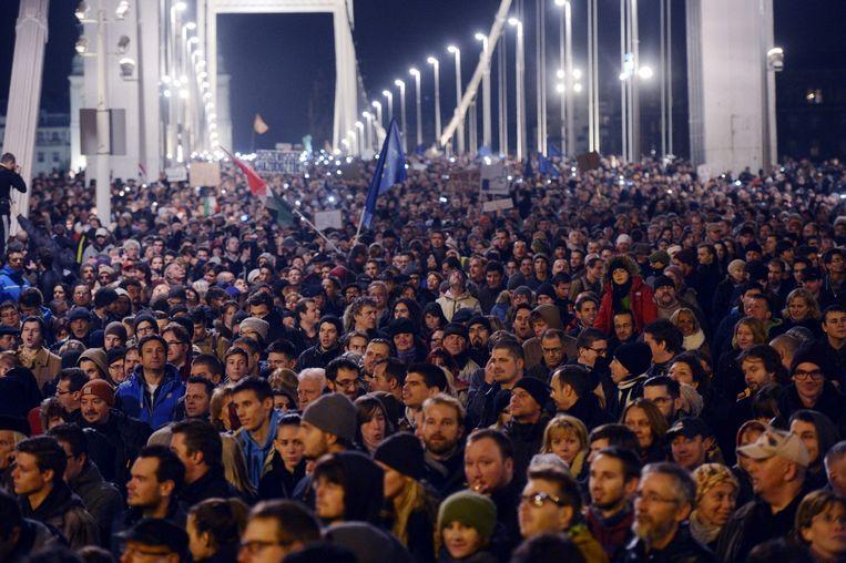 Duizenden Hongaren demonstreren op de Elisabeth-brug in Boedapest tegen de omstreden internetbelasting. Beeld ap