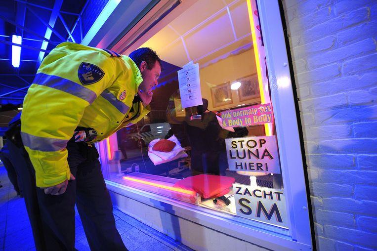 Een politieagent doorzoekt een peeskamer op het Baekelandplein in Eindhoven. Beeld ANP