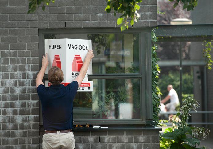 Een makelaar plaatst een Te Koop-bord op de ruit van een woning in Dordrecht.
