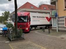 Vrachtwagen rijdt zich klem en zit muurvast in straat in Arnhem