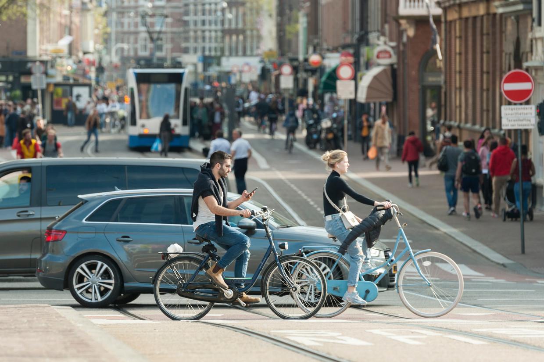 Auto's, fietsers en openbaar vervoer delen de weg in het centrum van Amsterdam. Beeld Shutterstock