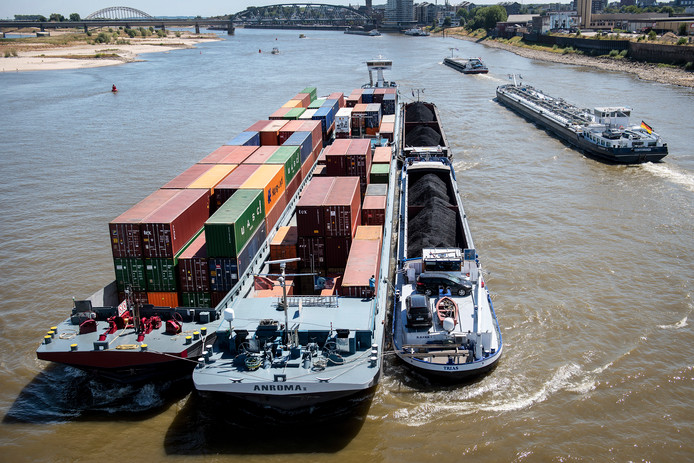 : Een collega-schipper heeft het vastgelopen vrachtschip Trias Obelix (rechts) weer losgetrokken, op de Waal bij Nijmegen.