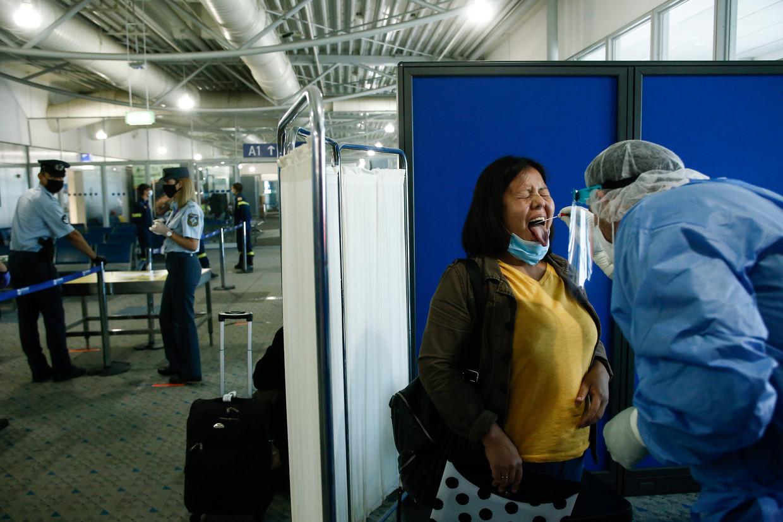 Een passagier van een vlucht uit Doha wordt gecheckt op coronavirus. Beeld EPA