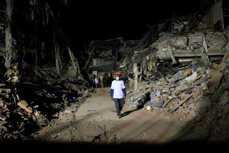 Een reddingswerker loopt weg van het ingestorte Ambacang Hotel in Padang, Indonesië. Drie dagen na de aardbeving wordt zaterdag nog steeds gezocht naar slachtoffers. (AP) Beeld AP