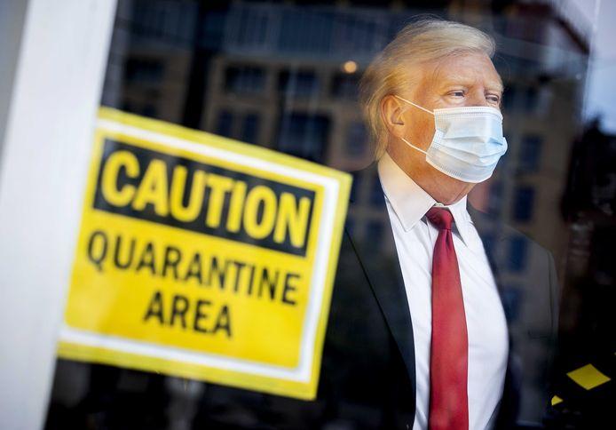Het wassen beeld van president Donald Trump is door Madame Tussauds in Amsterdam ook 'in quarantaine' geplaatst. Het beeld staat voorzien van een mondkapje voor het raam van Tussauds op de Dam.