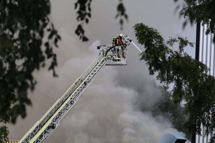 De ladder van de brandweer hangt boven het pand om het vuur te blussen.