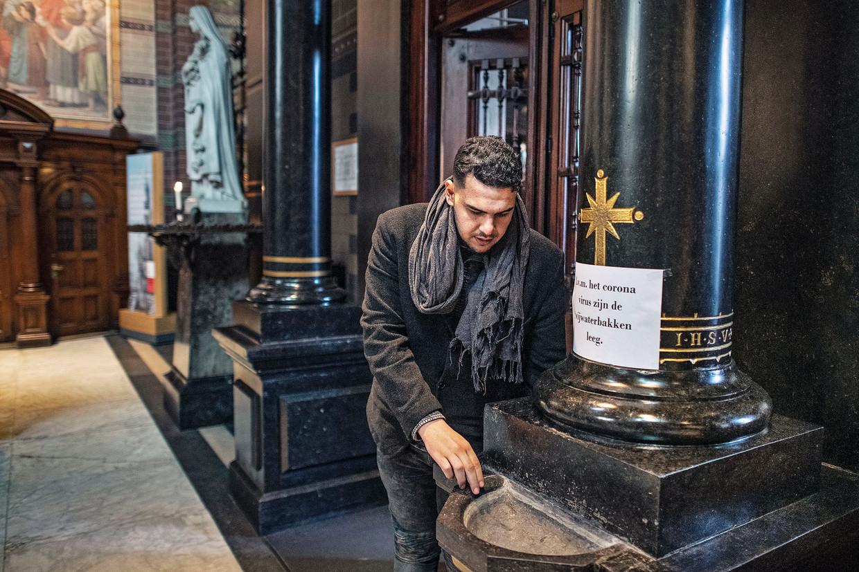 Een gelovige ziet tot zijn verbazing dat er geen water is in de wijwaterbakken is van de Basiliek van de H. Nicolaas in verband met het coronavirus. Beeld Guus Dubbelman / de Volkskrant