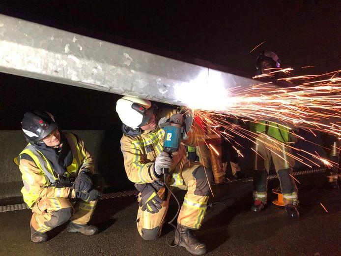 De brandweer is op dit moment de verlichtingspaal in stukken aan het snijden