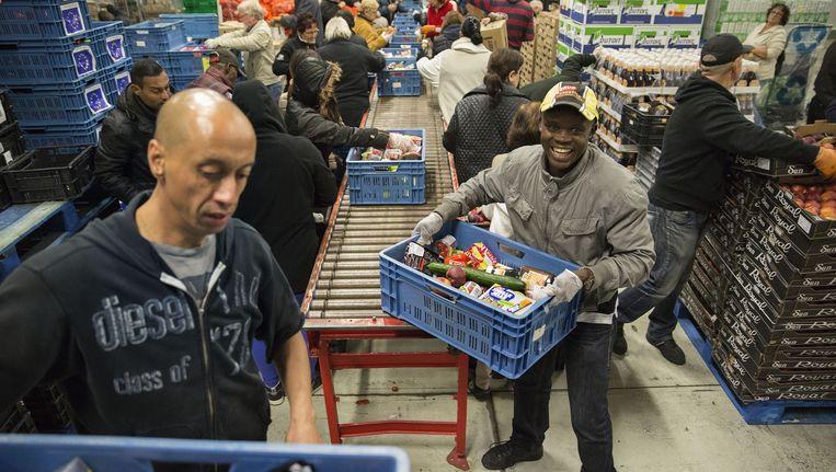 Vrijwilligers ruimen pakketten in bij de Voedselbank. Beeld Arie Kievit