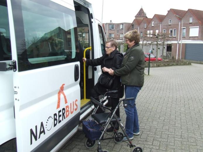 Vrijwillig chauffeur helpt passagier bij het instappen in de Naoberbus.