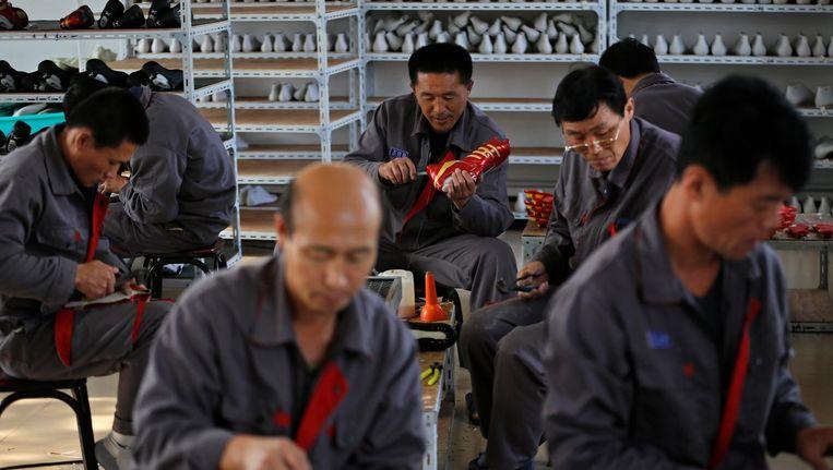 Noord-Koreaanse dwangarbeiders in een schoenenfabriek in China. Beeld reuters