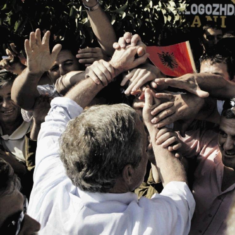 Juni 2007: Tijdens zijn bezoek aan Albanië wordt Bush¿ polshorloge gerold. (FOTO AP) Beeld AP