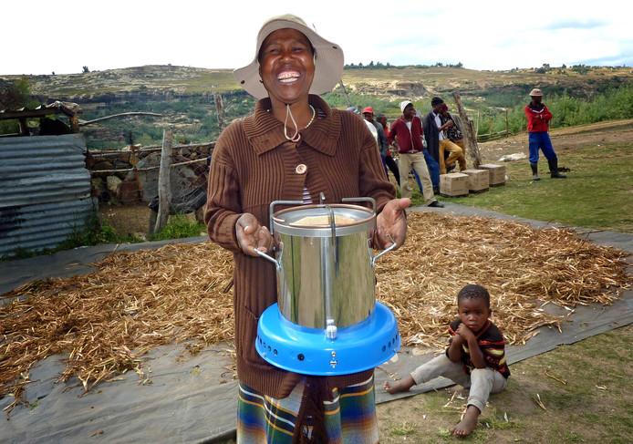 Een Afrikaanse moeder is blij met haar hightech-oven.