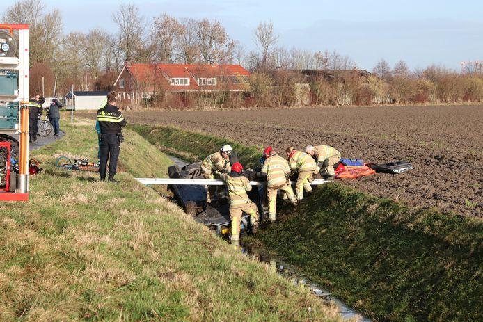 Brandweerlieden bevrijden de gewonde man uit zijn auto.
