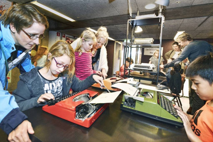 Kinderen aan de slag met een oude typemachine.