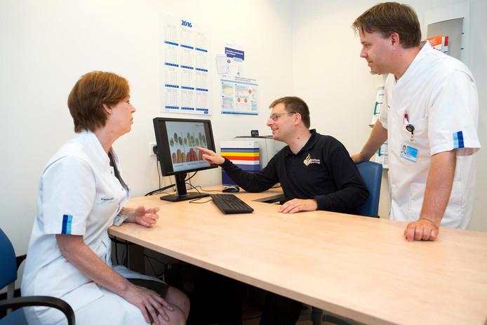 Internist oncoloog Ron Mathijssen, Sebastiaan Veelenturf van de Politie Den Haag en verpleegkundig specialist Leni van Doorn bespreken een vingerafdruk die zojuist bij een patiënt is afgenomen