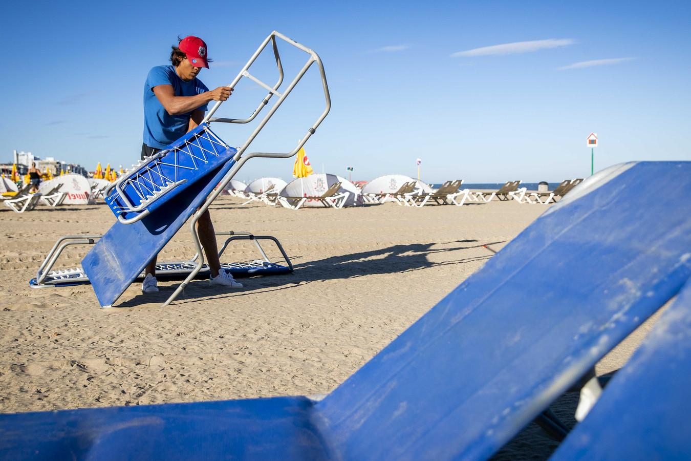 Een medewerker van een strandpaviljoen bereidt zich voor op de drukte. Het belooft een zomerse dag te worden, de komende dagen wordt het nóg warmer.