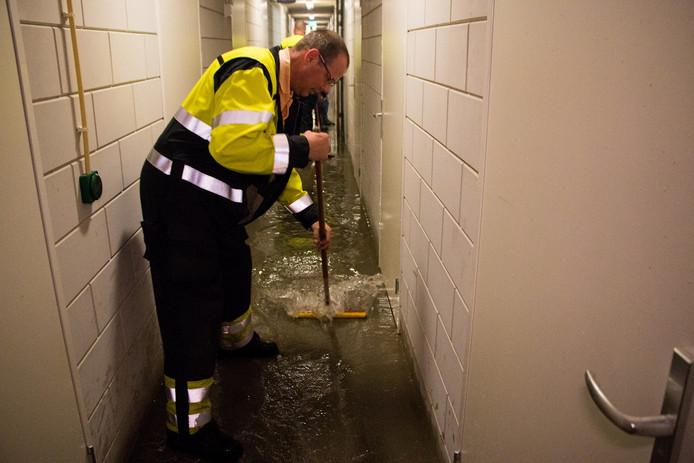 Brandweerlieden halen met trekkers het ergste van het water weg.
