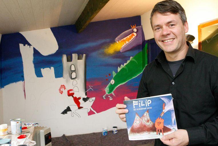Grafisch schilder Bart Peeters met het boekje 'De vliegende dino', dat hij en zijn zoon Filip maakten. Op basis van de tekeningen van de toen 6-jarige Filip maakt Bart nu de muurschildering in zijn atelier.