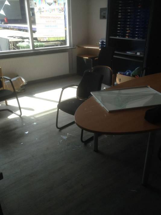 De beschadigde lijst op de tafel, het gesneuvelde glas ligt op de grond.