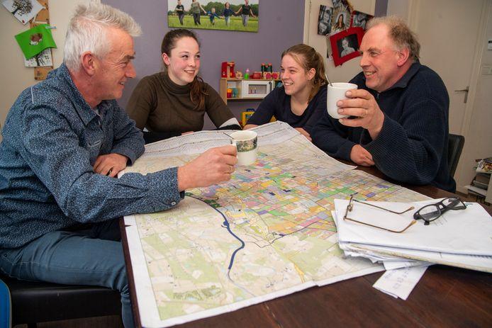 Albert Dankelman (links) bespreekt met Kim (links), Iris en René Hilgenkamp de kavelruil in het gebied. Op de kaart zijn met kleurtjes de verschillende percelen aangegeven.