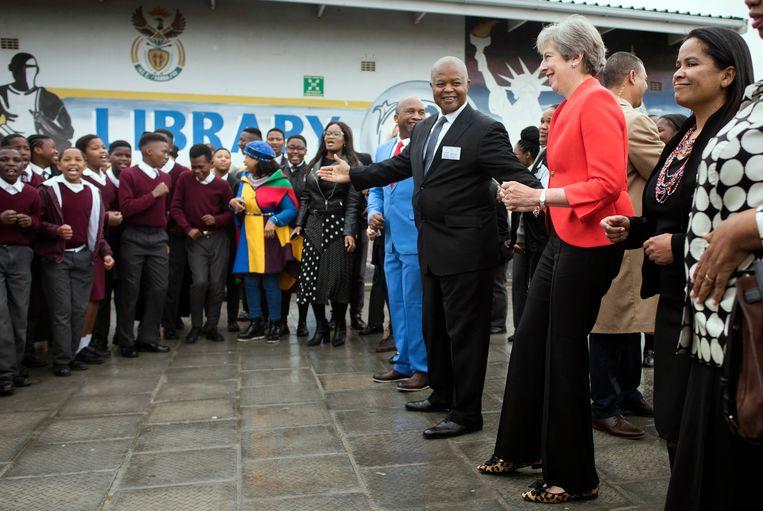 De Britse premier Theresa May danst dinsdag in Kaapstad mee met de leerlingen van de ID Mkhize High School. Beeld AP