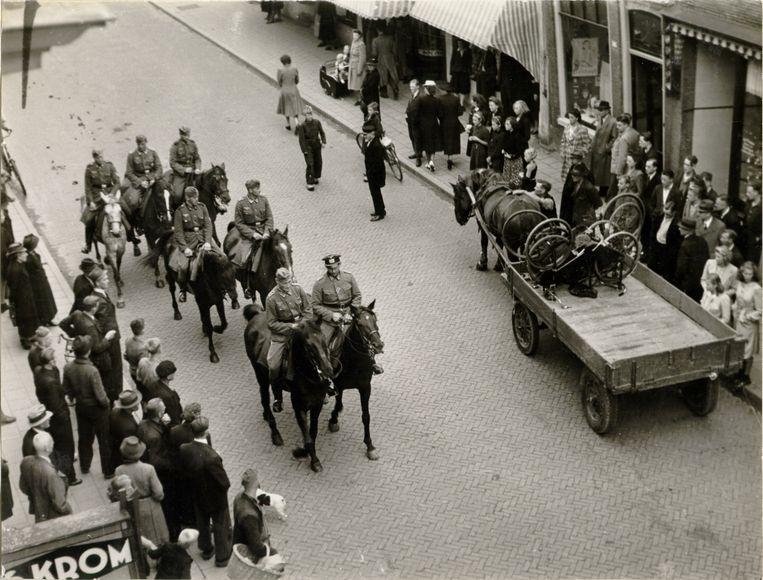 Hoorn, 1945. Nog in 1945 worden op het Grote Noord in Hoorn fietsen gevorderd en op een boerenkar geladen. Omstanders kijken toe terwijl een Duitse patrouille te paard passeert. Beeld Jan Dirk Osinga/ Negatievencollectie Osinga, Westfries Archief