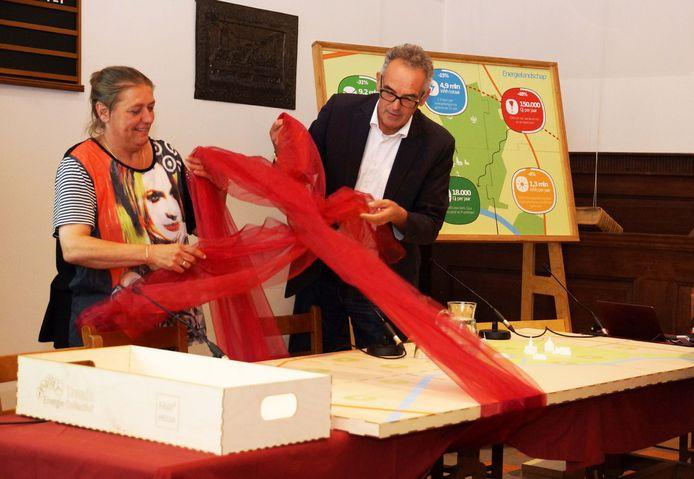 Archieffoto. Petra Kimmel van het Traais Energie Collectief en wethouder Hans Kuijpers van Drimmelen onthulden op een bijeenkomst van het collectief een energietafel. Met de tafel kunnen energieprojecten (en hun opbrengst) in Terheijden in beeld worden gebracht.