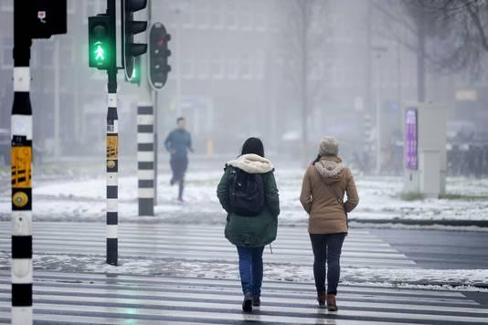 Twee vrouwen wandelen in restjes sneeuw.