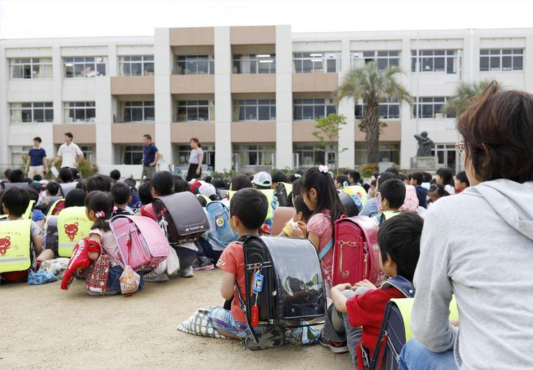 Kinderen zitten op het schoolplein, nadat ze uit hun schoolgebouw geëvacueerd werden na de aardbeving in Ikeda, in de Osaka prefectuur in west-Japan.