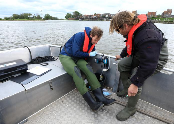 Bij Woudrichem nemen Thomas Kroon (links) en Jöran Janse van RAVON wederom een watermonster.