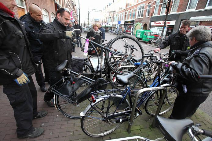 Verwijderen van fietsen die al tijden niet gebruikt zijn maar wel kostbare plekken vasthouden in de Weimastraat. FOTOGRAAF NICO SCHOUTEN