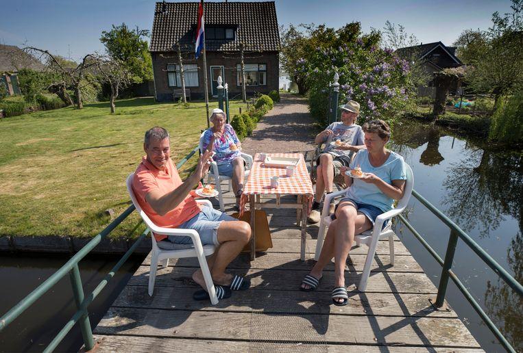 In Tienhoven eten de dorpelingen om half 12 gezamenlijk een gebakje in de voortuin.  Beeld Werry Crone