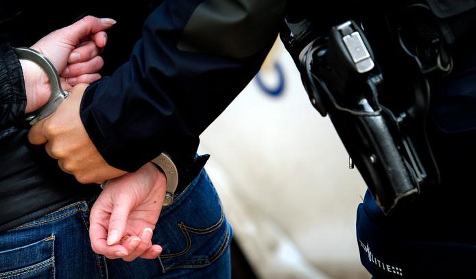 Een man wordt opgepakt door de politie.