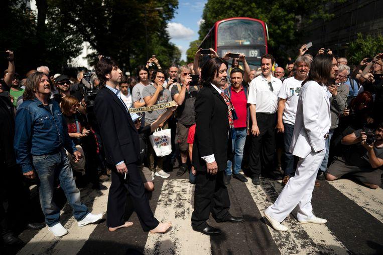 Het was gisteren vijftig jaar geleden dat The Beatles hun album Abbey Road uitbrachten, met op de hoes de beroemde foto van de bandleden op een zebrapad. Het jubileum veroorzaakte grote drukte in de Londense straat, waar honderden Beatles-fans de hoesfoto wilden namaken.   Beeld EPA