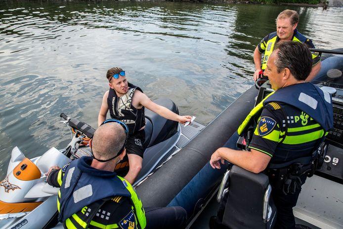 De waterpolitie controleert de bestuurder van een waterscooter. foto: ARIE KIEVIT