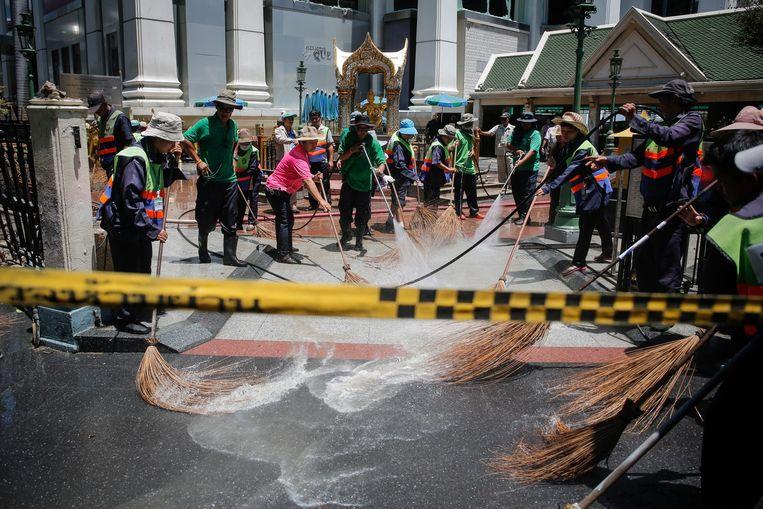 Schoonmakers van de gemeente maken de plek van de aanslag schoon, zodat iedereen in Bangkok snel weer kan doen alsof er niets is gebeurd. Beeld epa