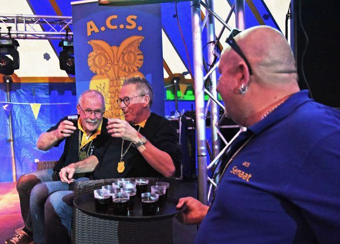De ereleden Rino Pieters (links) en Eric de Cocq toasten met gluhwein op het podium ter ere van 44 jaar carnaval.