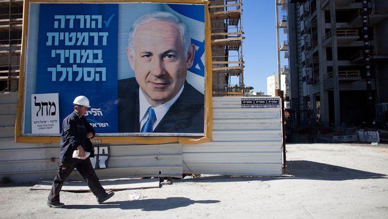 Premier Netanyahu kijkt vanaf een verkiezingsposters zijn kiezers aan Beeld getty